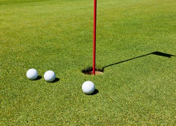 Three golf balls on the putting green, next to the hole